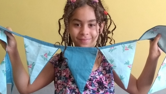Young girl holding blue and floral patterned bunting
